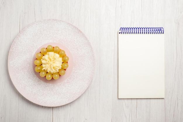 Draufsicht kleine sahnetorte mit trauben auf weißem schreibtisch obstkuchen dessertkuchen keksplätzchen