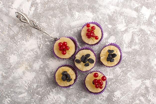 Draufsicht kleine schokoladenbrownies mit preiselbeeren auf dem hellen hintergrundkuchen-kekszucker-süßen backteig