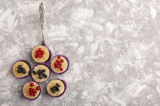 Draufsicht kleine schokoladenbrownies mit preiselbeeren auf dem hellen hintergrundkuchenkeks süßer backteig