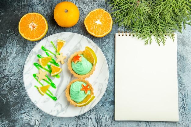 Draufsicht kleine torten mit grüner gebäckcreme und zitronenscheibe auf teller geschnittenen orangen-notizbuch auf dunklem tisch