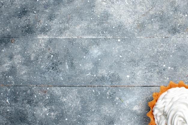 Draufsicht kleiner cremiger kuchen gebacken köstlich lokalisiert auf dem grauen hintergrundkuchenkeks süßer zuckerfotocreme