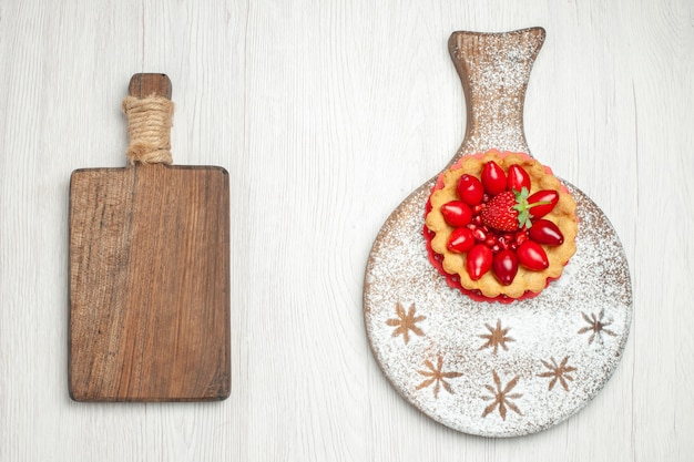 Draufsicht kleiner cremiger kuchen mit frischen früchten auf weißem schreibtisch