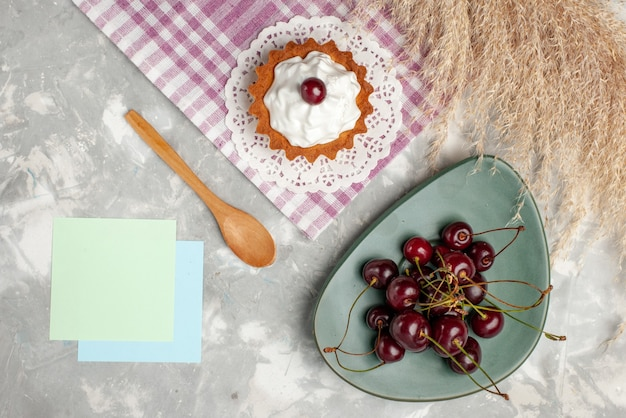 Draufsicht kleiner cremiger kuchen mit frischen sauerkirschen auf dem hellen hintergrund obstkuchen süße backcreme