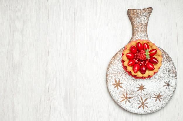 Draufsicht kleiner cremiger kuchen mit früchten auf hellweißem schreibtisch