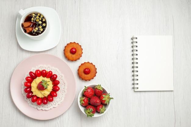 Draufsicht kleiner cremiger kuchen mit früchten und tasse tee auf weißem schreibtisch