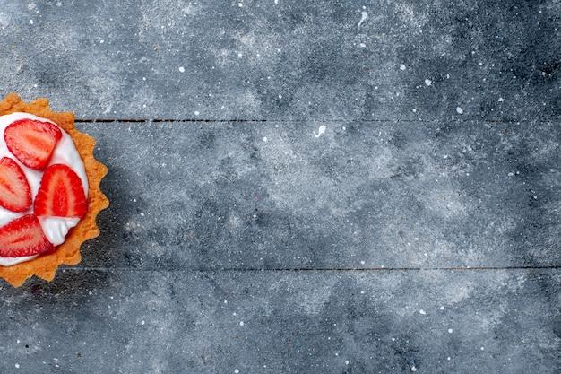 Draufsicht kleiner cremiger kuchen mit geschnittenen erdbeeren auf dem süßen farbfoto des grauen hintergrundfruchtbeerenkuchens