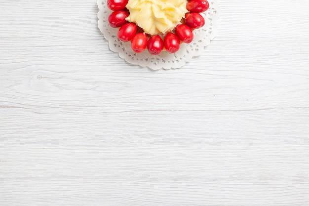 Draufsicht kleiner cremiger kuchen mit hartriegeln auf weißem schreibtisch