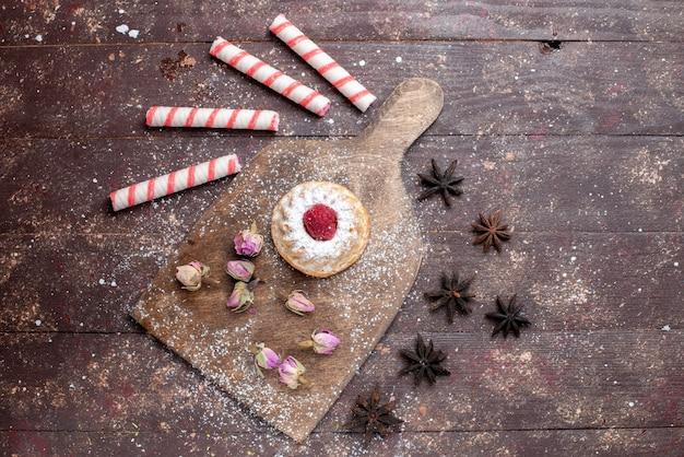 Draufsicht kleiner cremiger kuchen mit himbeere zusammen mit rosa stockbonbons auf dem braunen hölzernen hintergrundbonbon süßer zucker backen kuchen