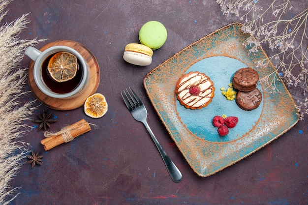 Draufsicht kleiner cremiger kuchen mit schokoladenkeksen und tasse tee auf einer dunklen oberfläche kekskuchen süße kuchen-zuckerkekse