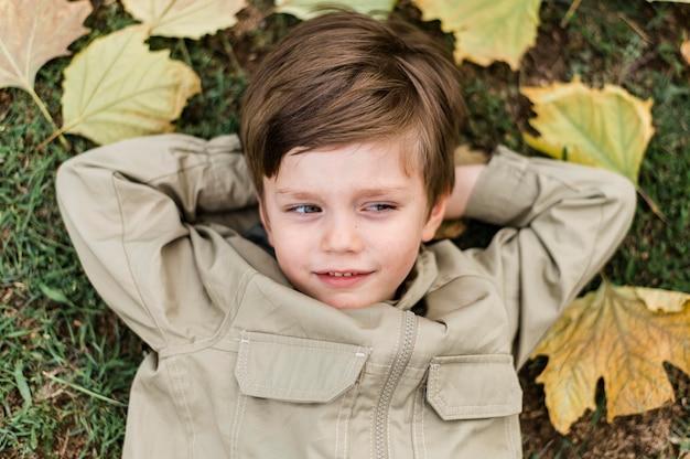 Draufsicht kleiner junge, der auf dem gras bleibt