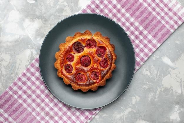 Draufsicht kleiner kirschkuchen innerhalb platte auf dem hellen schreibtischkuchen obst backen süßen tee