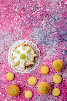 Draufsicht kleiner köstlicher kuchen mit geschnittenen fruchtkeksen auf der süßen zuckerfarbe des farbigen tischkuchens