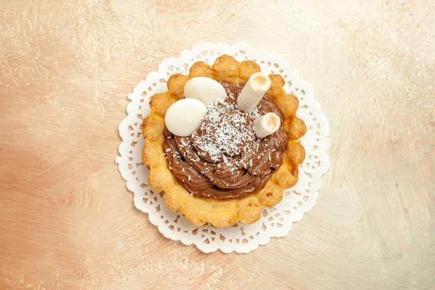 Draufsicht kleiner köstlicher kuchen mit sahne auf leichtem tischkuchenkuchen süßes dessert