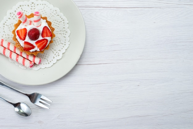 Draufsicht kleiner köstlicher kuchen mit sahne und geschnittenen erdbeeren innerhalb platte auf dem weißen hintergrund obstkuchen beere süßer zucker
