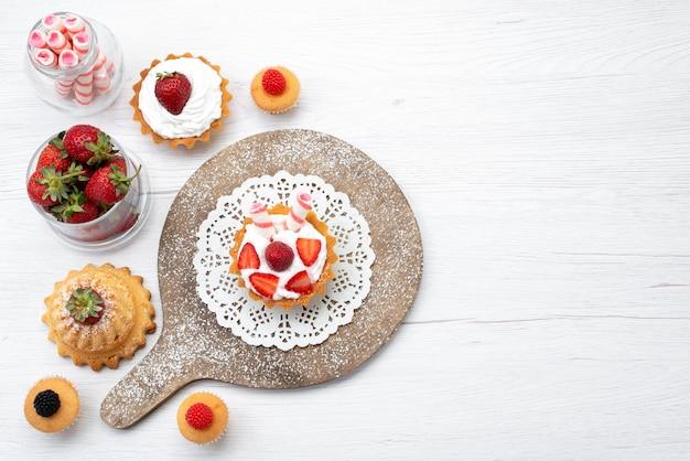 Draufsicht kleiner köstlicher kuchen mit sahne und geschnittenen erdbeerkuchen auf dem weißen hintergrundkuchenbeere süß backen obst backen