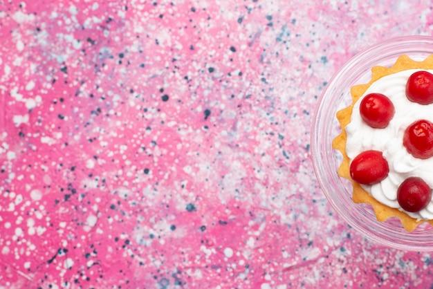 Draufsicht kleiner köstlicher kuchen mit sahne und roten früchten auf der hellen oberfläche zuckersüß