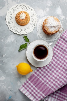 Draufsicht kleiner köstlicher kuchen mit tee und saurer zitrone auf dem hellen schreibtischkuchenkeks süße keksfarbe