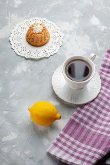 Draufsicht kleiner köstlicher kuchen mit tee und saurer zitrone auf der hellen schreibtischkuchenkeks-süßen keksplätzchenfarbe