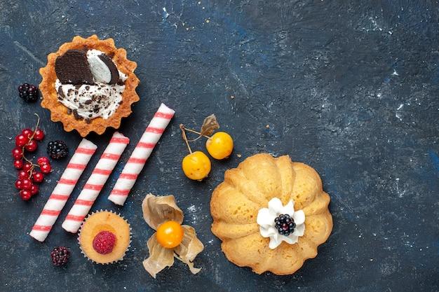 Draufsicht kleiner köstlicher kuchen zusammen mit keks- und rosa stockbonbonfrüchten auf dem dunklen schreibtischkekskuchen süße frucht