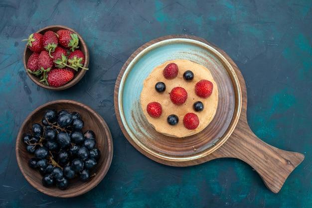 Draufsicht kleiner kuchen mit frischen erdbeeren auf der dunkelblauen oberfläche