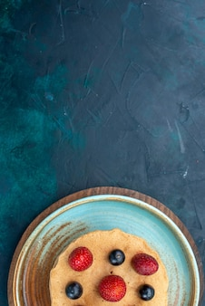 Draufsicht kleiner kuchen mit frischen erdbeeren drauf auf dem dunkelblauen schreibtisch
