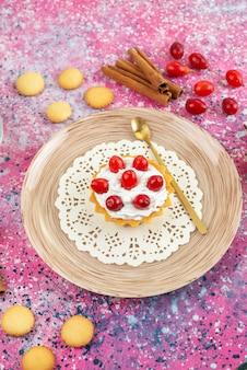 Draufsicht kleiner kuchen mit frischer sahne und frischen früchten zusammen mit zimt auf dem hellen schreibtischkeks