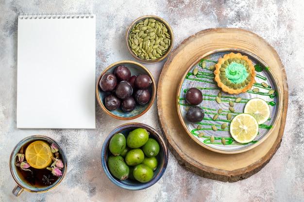 Draufsicht kleiner kuchen mit früchten und tee