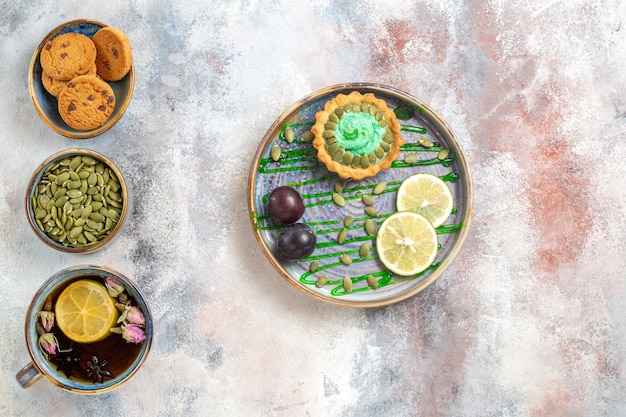 Draufsicht kleiner kuchen mit früchten und tee Kostenlose Fotos