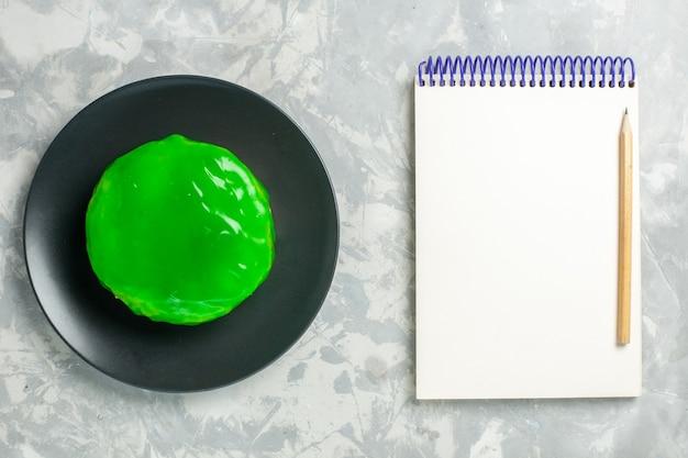 Draufsicht kleiner kuchen mit grünem zuckerguss und notizblock auf weißem oberflächenkuchen-keks-süßem zuckerkeks