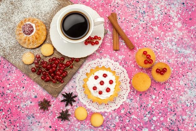 Draufsicht kleiner kuchen mit sahnekeksen frische preiselbeeren zusammen mit tasse kaffee und zimt auf dem farbigen oberflächenkeks