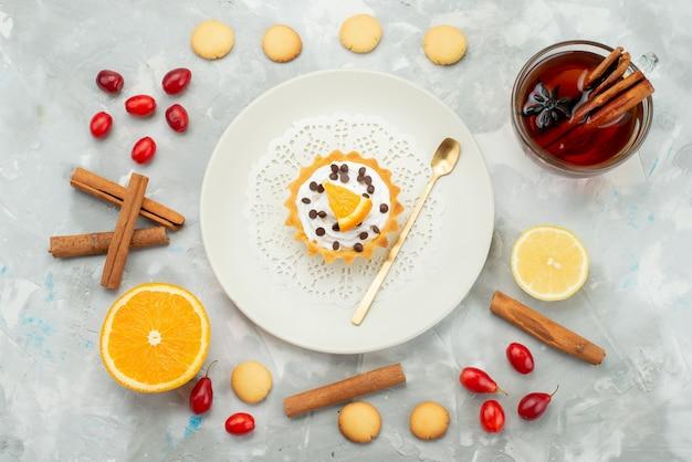 Draufsicht kleiner kuchen mit tee-zimtplätzchen auf der hellen oberfläche