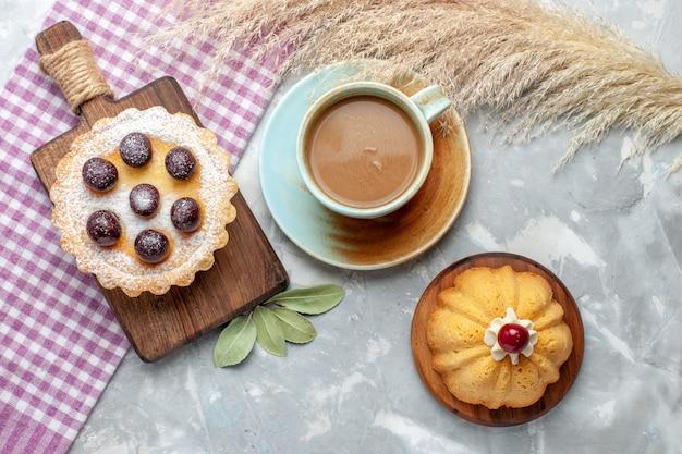 Draufsicht kleiner leckerer kuchen mit fruchtzucker pulverisiert zusammen mit milchkaffee auf leichtem tischkuchen kekskuchen süßer zucker