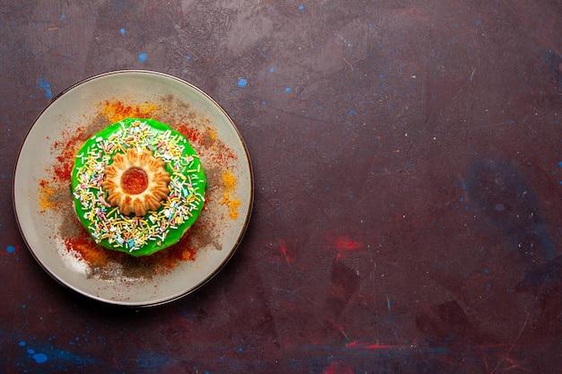 Draufsicht kleiner leckerer kuchen mit grüner creme auf dem dunklen schreibtisch