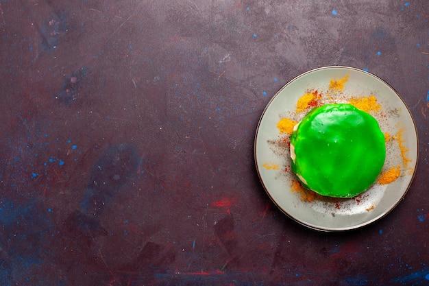 Draufsicht kleiner leckerer kuchen mit grüner creme im teller auf dem dunklen schreibtisch