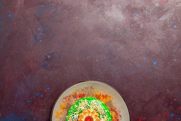 Draufsicht kleiner leckerer kuchen mit grüner creme im teller auf der dunklen oberfläche