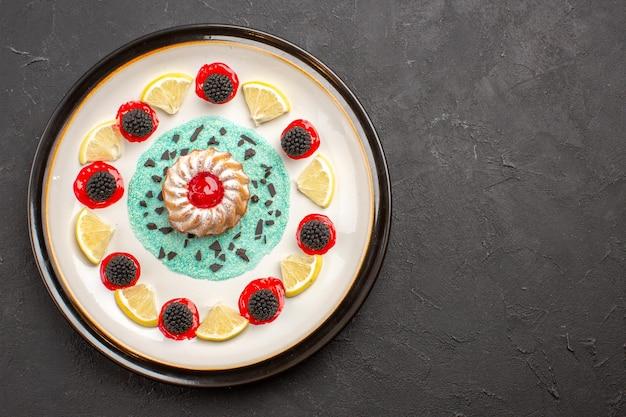Draufsicht kleiner leckerer kuchen mit konfitüren und zitronenscheiben im teller auf dem dunklen hintergrund obst zitrus keks keks süß