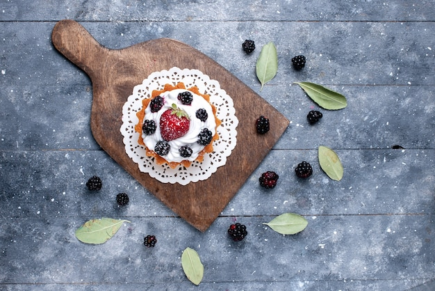 Draufsicht kleiner leckerer kuchen mit sahne und beeren auf dem hellen hintergrundkuchenkeks süßer zucker backen beere