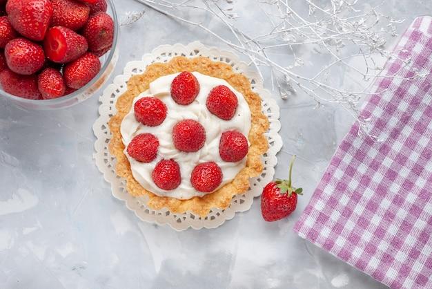 Draufsicht kleiner leckerer kuchen mit sahne und frischen roten erdbeeren auf der leichten schreibtischkuchen-fruchtkekscreme