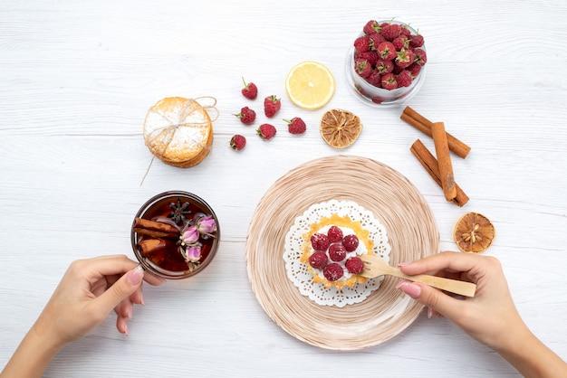Draufsicht kleiner leckerer kuchen mit sahne und himbeeren zusammen mit sandwichkeksen zimttee auf dem hellen tisch obstbeerenkuchen keks süß