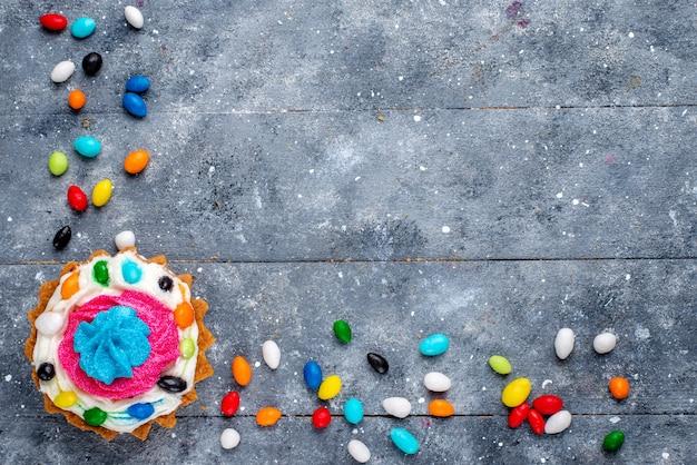 Draufsicht kleiner leckerer kuchen mit sahne und verschiedenen bunten bonbons über dem hellen hintergrundbonbon süßes farbkuchenfoto