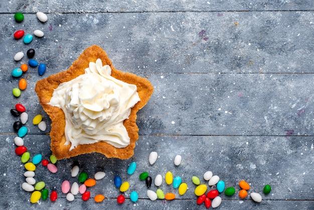 Draufsicht kleiner leckerer kuchen mit sahne und verschiedenen bunten bonbons überall auf dem hellen hintergrund süßigkeiten süßer zuckerfarbkuchen