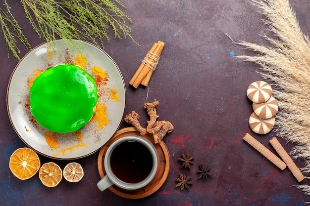 Draufsicht kleiner leckerer kuchen mit tasse tee auf dunkelviolettem schreibtisch