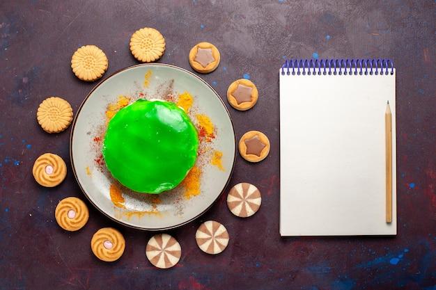 Draufsicht kleiner leckerer kuchen mit verschiedenen keksen auf dunklem schreibtisch