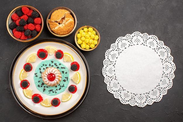 Draufsicht kleiner leckerer kuchen mit zitronenscheiben und bonbons auf dem dunklen hintergrund kekskuchen obst zitrusplätzchen süß