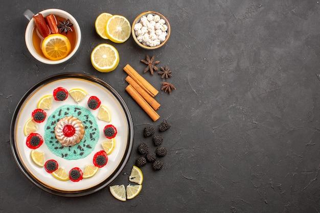 Draufsicht kleiner leckerer kuchen mit zitronenscheiben und tasse tee auf dem dunklen hintergrund obst zitrus keks keks süß