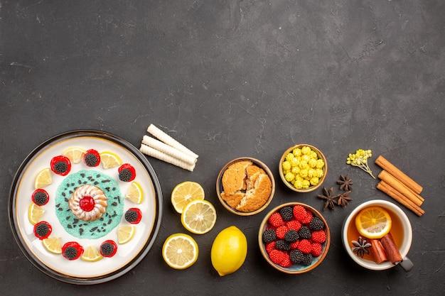 Draufsicht kleiner leckerer kuchen mit zitronenscheiben und tasse tee auf dunklem hintergrund