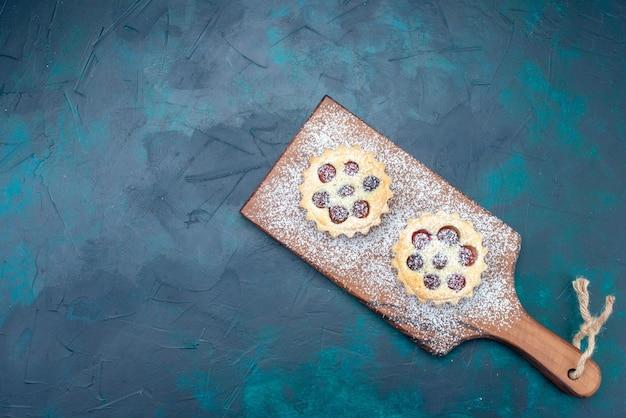 Draufsicht kleiner leckerer kuchen mit zuckerpulver und kirschen auf dem blauen schreibtisch obstkuchen keks süße fotofarbe