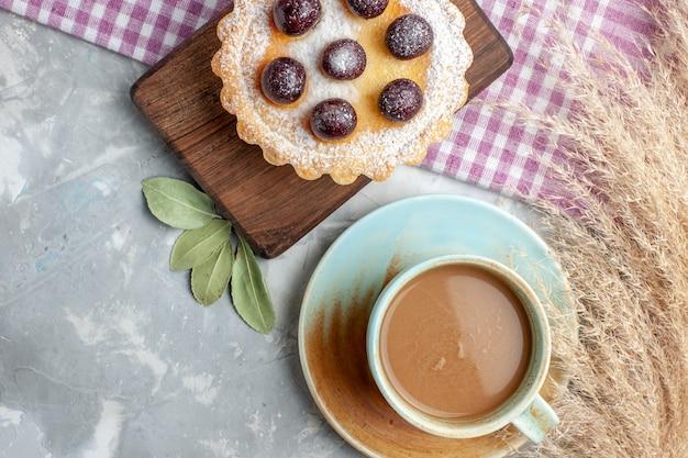 Draufsicht kleiner leckerer kuchen mit zuckerpulver und kirschen zusammen mit milchkaffee auf dem hellen schreibtisch obstkuchenkeks süße farbe