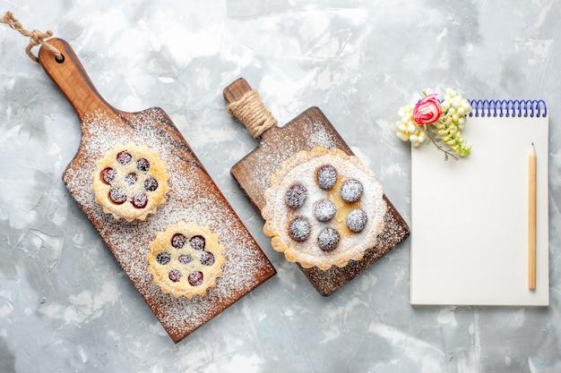 Draufsicht kleiner leckerer kuchen mit zuckerpulver und kirschen zusammen mit notizblock auf dem hellen schreibtisch obstkuchen keks süße farbe