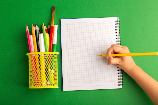 Draufsicht kleines kind, das etwas auf heft auf der grünen oberfläche zeichnet und schreibt